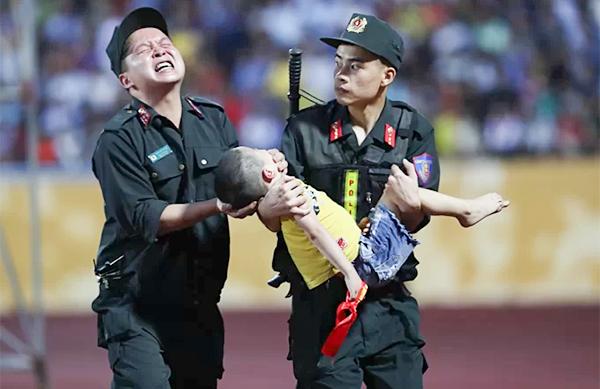 Chiến sĩ cảnh sát cơ động nén đau để ngăn fan nhí nuốt lưỡi trên sân Thiên Trường chiều 4/8. Ảnh: Đức Đồng.