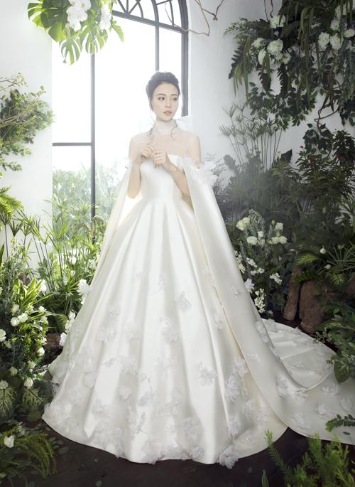Đàm Thu Trang thích mặc váy kín đáo nên Trần Hùng đã sáng tạo váy có cổ illusion, đính nơ, thể hiện sự nhẹ nhàng, tính cách hiền lành, giản dị của cô dâu.