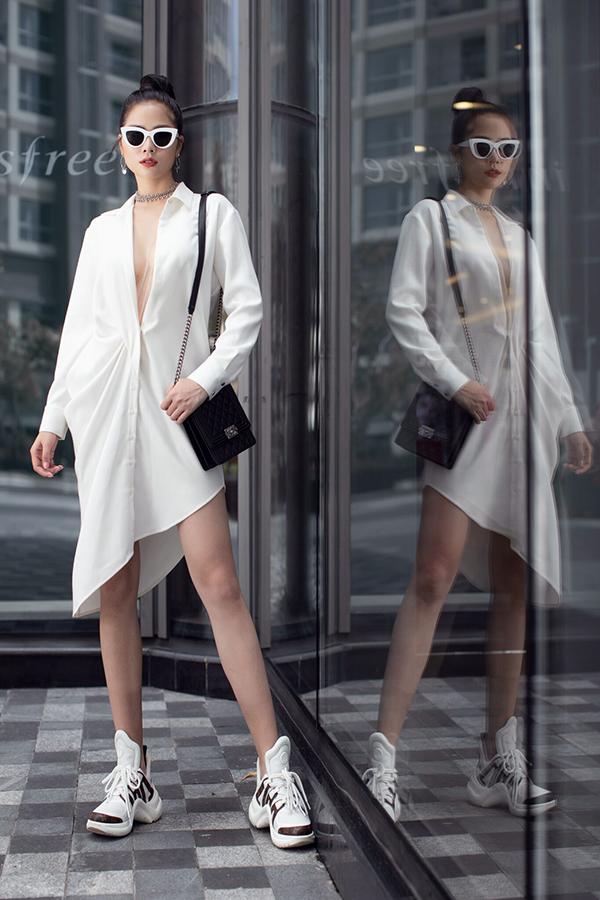 Người đẹp mặc áo sơ mi hờ hững mở cúc xuống gần đến rốn. Cô hoàn thiện vẻ dành điệu bằng sneakers của Louis Vuitton, túi Chanel và kính mắt Miu Miu. Hoàng Hạnh tạo điểm nhấn vào vòng một bằng cách đeo thêm bộ dây chuyền lấp lánh.