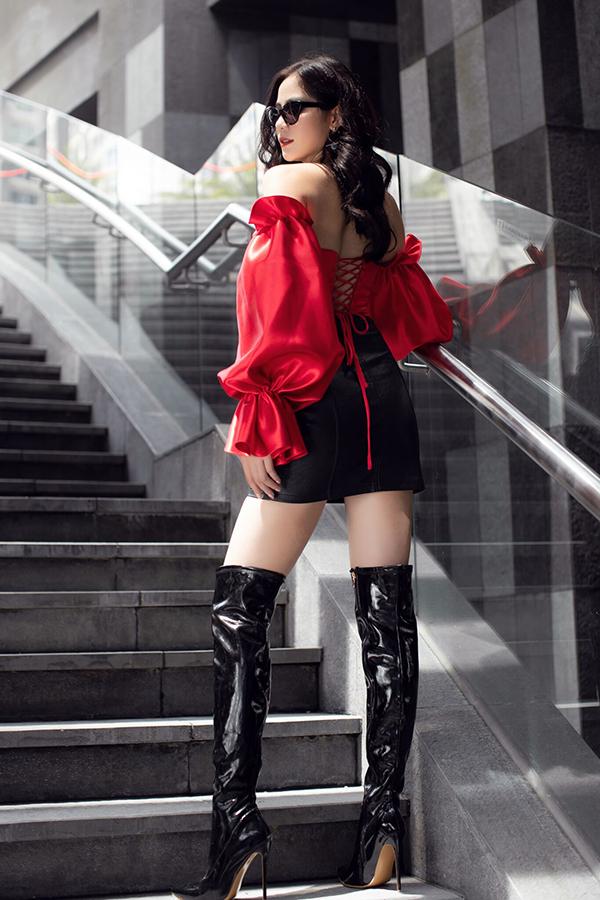 Cô hoàn thiện vẻ sành điệu, cá tính bằng boot da bóng cao cổ và kính đen.