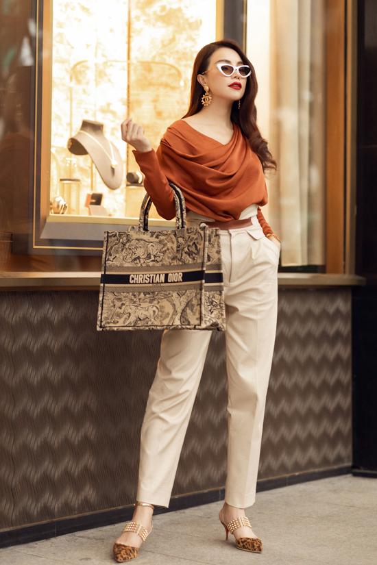 Để khoe vẻ đẹp sang trọng, nữ quyền những chiếc áo sơ mi nâu được Trà Ngọc Hằng kết hợp cùng quần dài lưng cao, nhấn cùng chiếc túi xách big size của Dior.