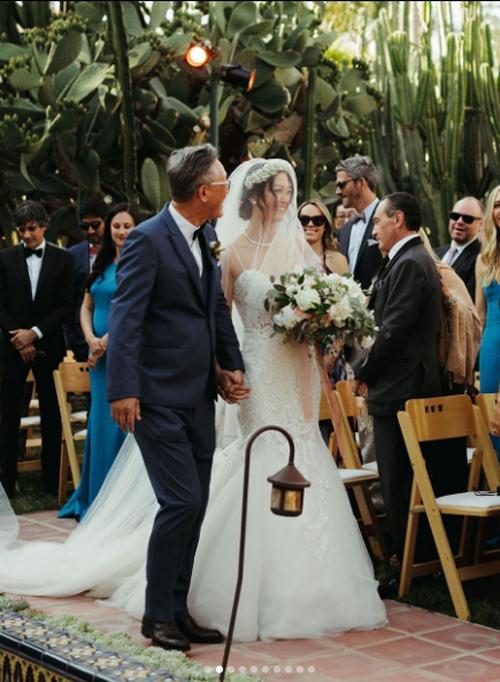 Cô dâu Michelle được miêu tả là đội chiếc vương miện kết bằng hoa baby, khăn voan trùm đầu dài thướt tha và đôi má ửng hồng khi được cha nắm tay dắt vào lễ đường.