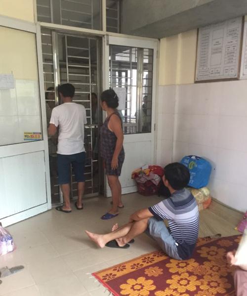 Người nhàchăm sóc bệnh nhân ở  khoa Hồi sức cấp cứu của Viện bỏng Quốc gia Lê Hữu Trác (Hà Đông, Hà Nội), trò chuyện với người đến thăm qua cánh cổng sắt cách ly giữa khu điều trị với bên ngoài chiều 12/8.
