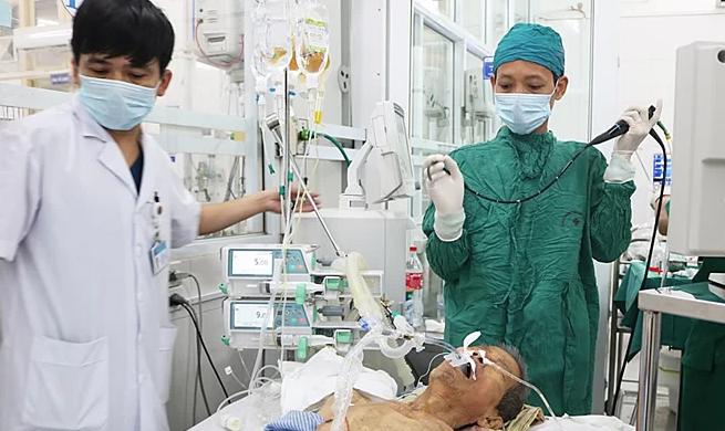 Bác sĩ nội soi gắp cầu răng giả khỏi phế quản cụ ông. Ảnh: Tạ Khánh.