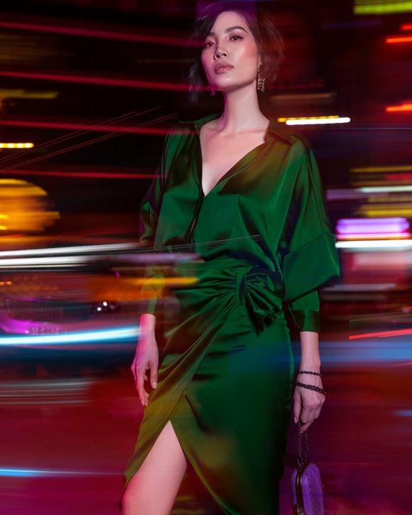 Chọn phong cách hiện đại cho bộ ảnh street style mới, Vũ Cẩm Nhung diện set đồ lụa xanh mềm mại gồm sơ mi mở cổ sâu và chân váy quấn xếp nếp, kết hợp clutch tím nổi bật.