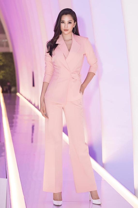 Hoa hậu Tiểu Vy kín đáo khi chọn thiết kế vest có điểm nhấn là phần cổ cách điệu. Sắc hồng ngọt ngào tôn vẻ đẹp nữ tính cho người đẹp 19 tuổi. Để hoàn thiện tổng thể, Tiểu Vy phối giày cao gót mũi nhọn và tối giản phụ kiện đi kèm.