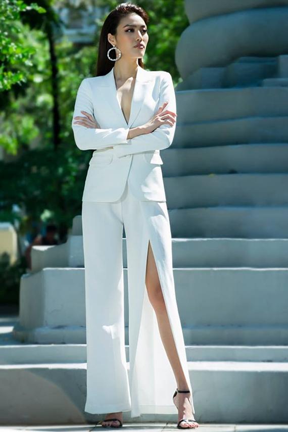 Lan Khuê lấp ló vòng một trong bộ suit trắng xẻ ngực. Thiết kế quần ống loe cắt xẻ của Lê Ngọc Lâm còn giúp Hoa khôi Áo dài khoe chân thon. Sandals quai mảnh tạo cảm giác thanh thoát cho ngoại hình.