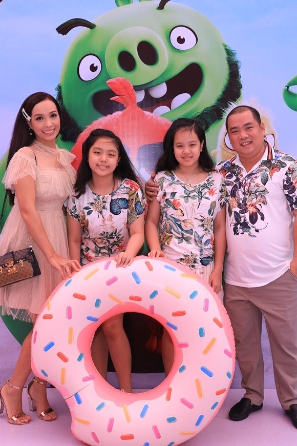 Gia đình siêu mẫu Thúy Hạnh - nhạc sĩ Minh Khang cùng đi xem phim tại TP HCM. Thúy Hạnh xuất hiện điệu đà vớiváy ren hồng pastel, kết hợp sandal cùng màu, còn Minh Khang diện áo thun họa tiết hoa lá ton sur ton với hai con gái Suli (thứ hai từ phải sang) và Suti.