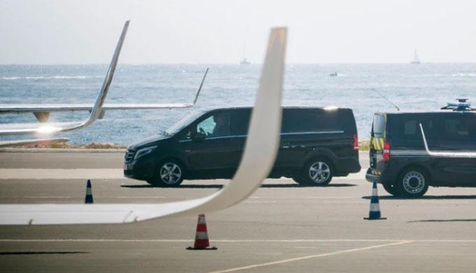 Cặp vợ chồng rời khỏi phi trường trên Mercedes đen. Ảnh: Eliot Press.