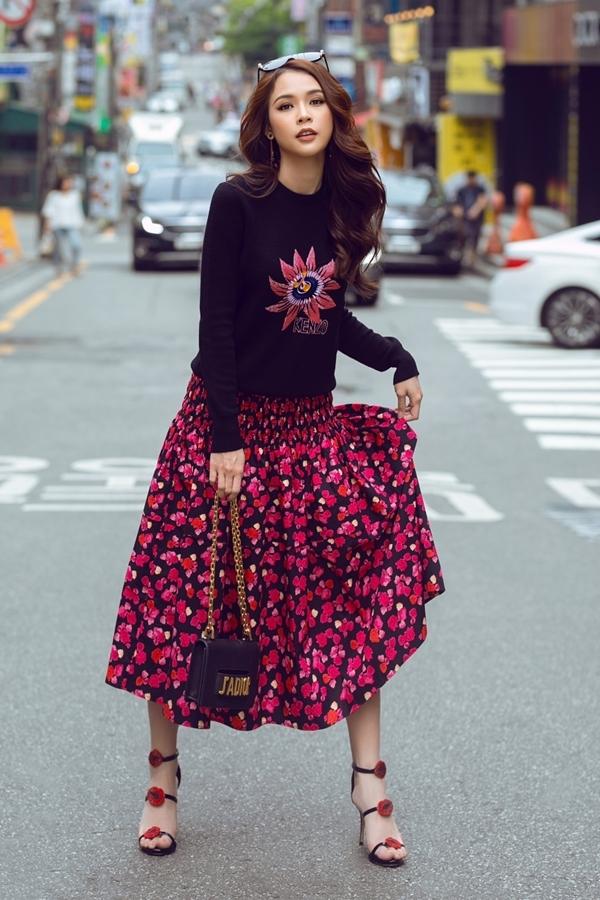 Nữ diễn viên theo đuổi phong cách nữ tính khi phối áo len thêu và chân váy hoa. Để hoàn thiện vẻ ngoài, cô bổ sung thêm mắt kính, giày và túi xách hàng hiệu.