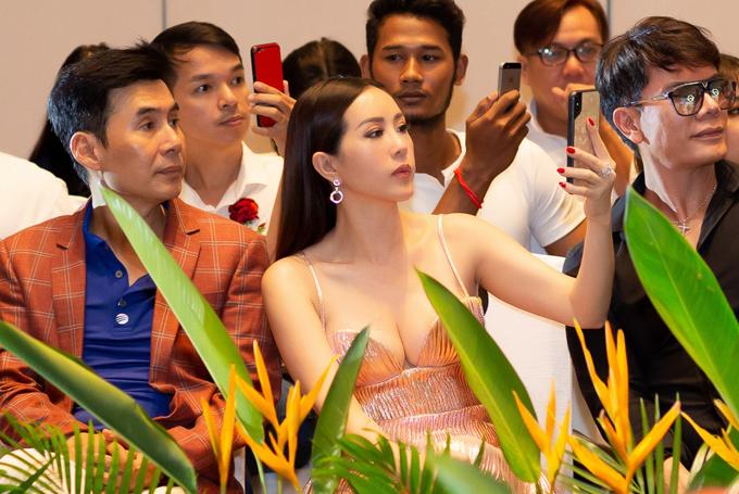 Ngồi bên ca sĩ Đoan Trường (trái), Thu Hoài chăm chú dùng điện thoại ghi lại hình ảnh dàn trai đẹp tranh tài tại Mister Vietnam năm nay.
