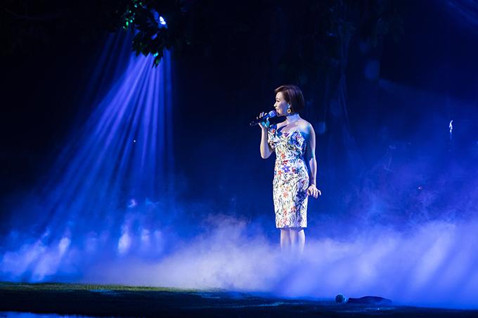 Uyên Linhca sĩ nhỏ bé khi đứng giữa sân khấu của Trung tâm Hội nghị Quốc gia Hà Nội với bộ đầm cúp ngực bó sát và hát Em về tóc xanh.
