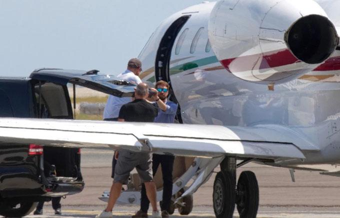 Hoàng tử Harry lên máy bay sau vợ. Anh luôn đội mũ lưỡi trai dường như để tránh bị chụp rõ mặt. Ảnh: The Mega Agency.