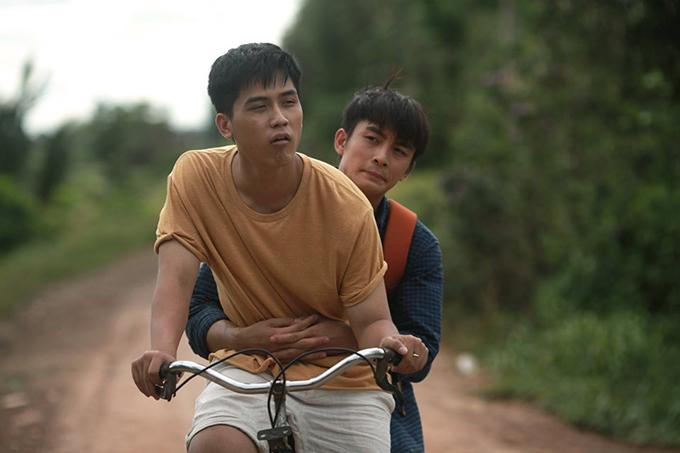 Văn (Lãnh Thanh) ôm Ian trên xe đạp trong một cảnh phim.