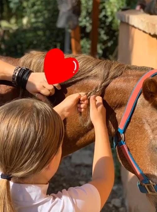 Becks cũng đăng tải ảnh con gái cưng giúp tết bờm cho ngựa...
