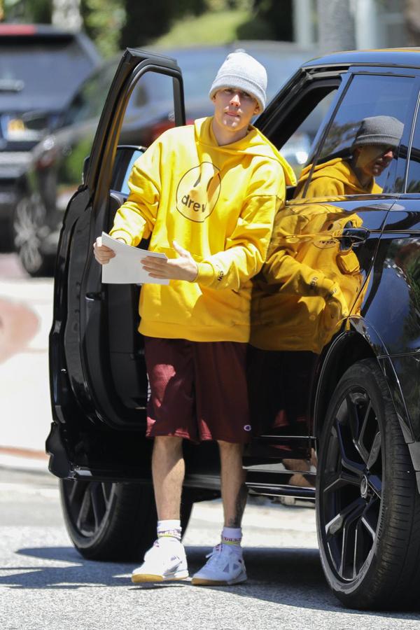 Mặc áo Drew nổi bật trên phố, Justin Bieber dừng xe bên đường, cầm tập giấy sticker đi tìm nơi dán.