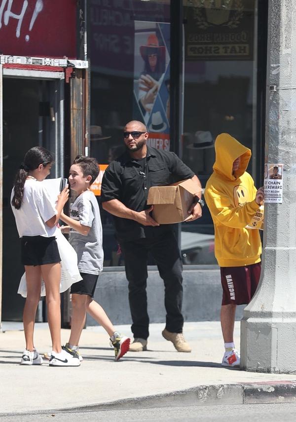 Trong khi vệ sĩ bê thùng giấy, Justin cặm cụi dán ở cột điện.