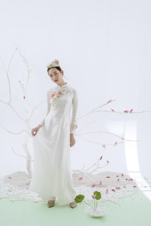 Áo dài cô dâu mang phom dáng truyền thống với cổ trụ thấp, tay áo dài. Điểm nhấn trên thân áo là họa tiết hoa 3D như gợi nhắc đến tình yêu ngọt ngào, đắm say của uyên ương.