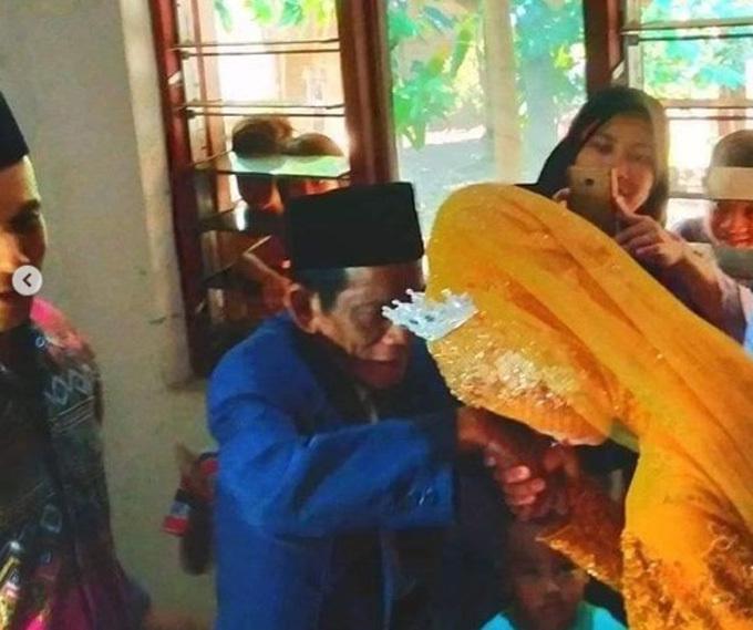 Nuraeni hôn tay chồng 83 tuổi khi làm lễ cưới. Ảnh: Grid.