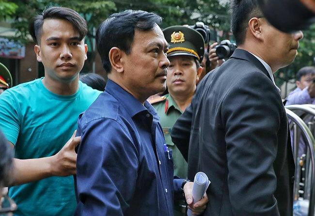 Ông Linh được cảnh sát bảo vệ che chắn khi vào tòa sáng23/8. Ảnh: Hữu Khoa.