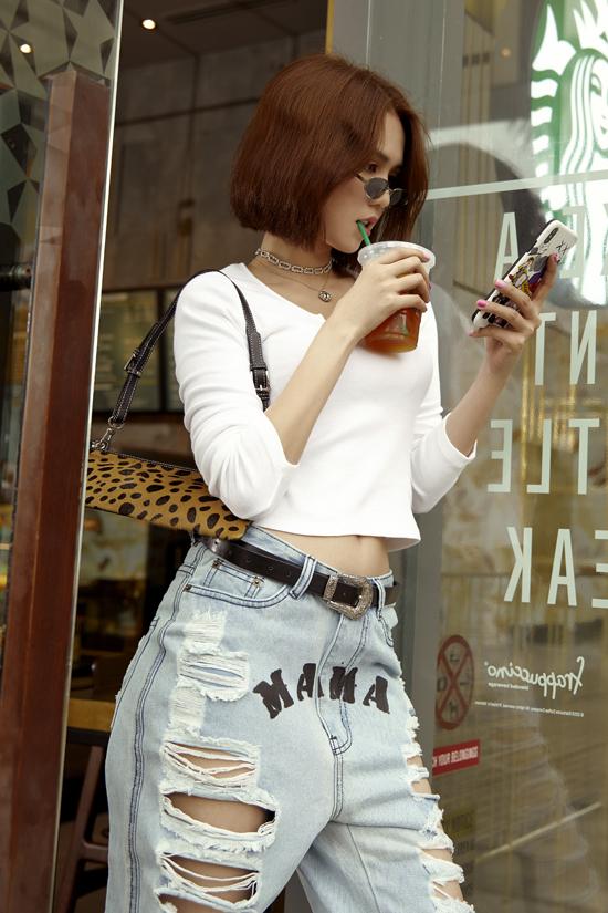 Quần jeans rách đáy thụng, áo hở eo được người đẹp phối hợp cùng nhau. Mốt shoulder bag cũng được Ngọc Trinh thể hiện một cách khéo léo để tăng vẻ sành điệu.