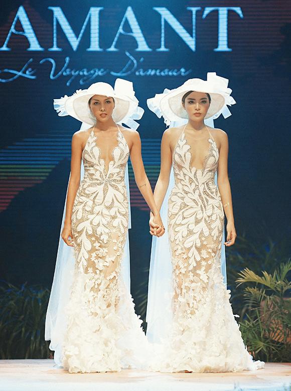 Trang phục thực hiện trên nền chất liệu xuyên thấu với phom dáng ôm khít, xẻ ngực sâu sexy giúp đôi bạn thân phô diễn hình thể nóng bỏng.
