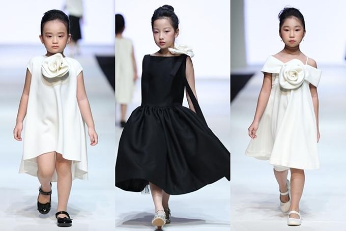 Dù là trang phục dành cho trẻ em, BST mang đậm dấu ấn Đỗ Mạnh Cường với 2 sắc đen, trắng, điểm nhấn là bông hoa lớn xếp li đặc trưng và các form váy suôn, bồng, cầu vai và hình khối 3D đã gắn liền với tên tuổi của anh.