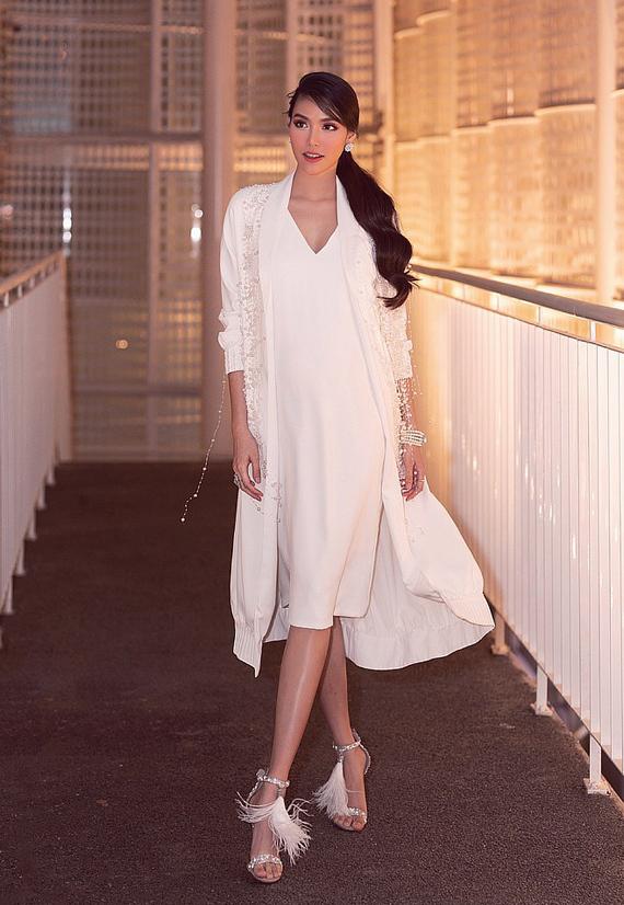 Lan Khuê diện cây trắng tham dự Vietnam Junior Fashion Week. Theo Tân Đà Lạt, phom váy suông kết hợp áo choàng dáng dài ton-sur-ton mềm mại không chỉ giúp người đẹp che khéo bụng bầu 6 tháng mà còn đem tới cho cô vẻ thanh lịch, yêu kiều.