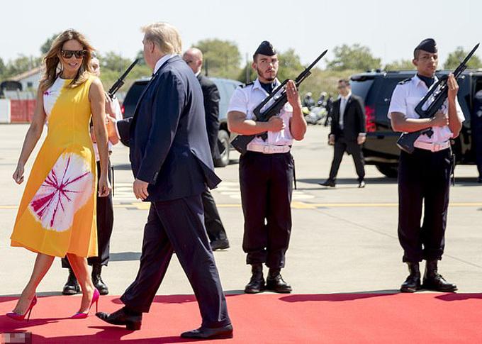 Hai người lính liếc mắt nhìn theo bà Melania khi bà cùng chồng đáp sân bay Biarritz, Pháp, hôm 24/8. Ảnh: AP.
