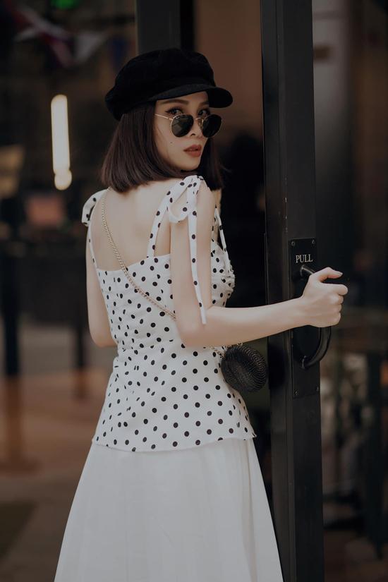 Thời trang dạo phố đầu thu của ca sĩ Yến Trang nhẹ nhàng với áo hai dây chấm bi đi cùng chân váy midi theo phong cách retro.
