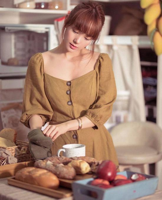 Minh Hằng bỗng trở nên dịu dàng chi khoác lên mình mẫu váy cổ điển thiết kế trên chất liệu vải thô vàgam màu trầm ấm.