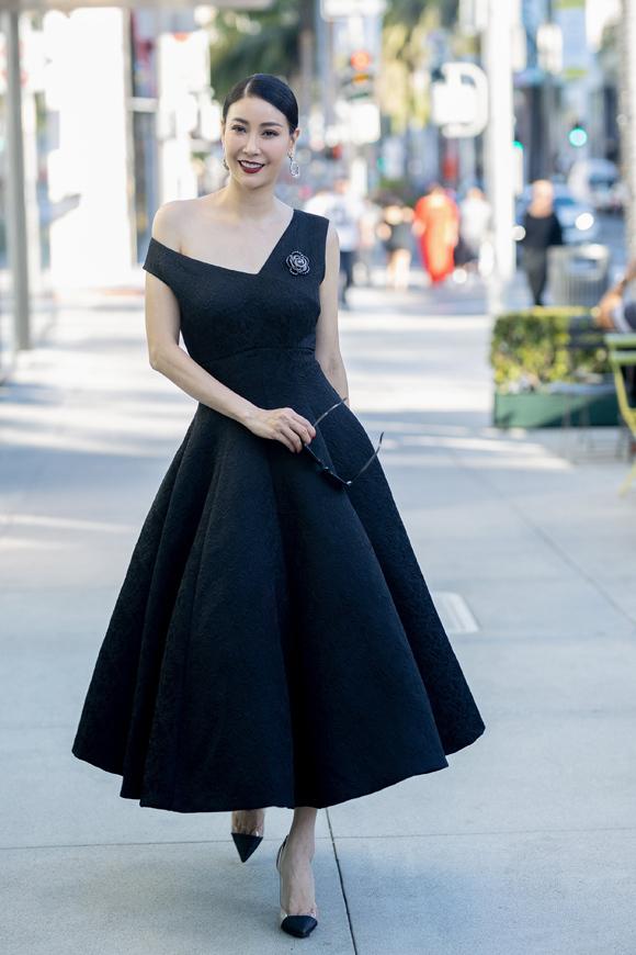 Hà Kiều Anh điệu đà trong chiếc váy lệch vai xòe rộng bồng bềnh, in họa tiết chìm tinh tế. Hoa hậu Việt Nam 1992 kết hợp xiêm y cùng phụ kiện của Chanel, nhẫn kim cương và đồng  hồ Rolex xa xỉ.