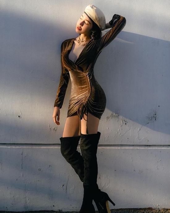 Elly Trần khoe hình thể đồng hồ cát với váy nhung kiểu rút dây. Cô kết hợp trang phục sexy cùng bốt cao qua gối và mũ beret.