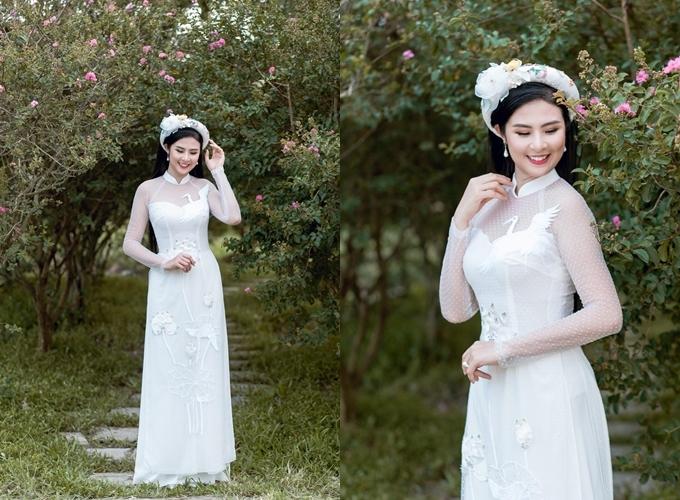 Trên những thước vải lụa và ren trắng là hình ảnh chim hạc và hoa sen trắng được thêu tay tỉ mỉ, sinh động. Biểu tượng chim hạc trên tà áo dài tượng trưng cho sự may mắn, hạnh phúc và bền vững. NTK - Hoa hậu Ngọc Hân chọn lựa họa tiết bông sen nhẹ nhàng, thanh khiết mang ý nghĩa về vẻ đẹp thuần khiết, dung dị của phái nữ. Ngọc Hân điểm những hạt cườm óng ánh trên tà áo lụatựa những giọt sương khẽ đọng trên cành hoa buổi sớm mai. Áo được bán với giá 10 triệu đồng, giá thuê 4 triệu đồng. Trang phục: Ngọc Hân Boutique