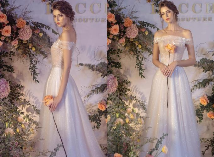 Mẫu đầm mang tên Adomie có kiểu dáng trễ vai làm từ chất liệu voan mỏng, giúp che đi khuyết điểm bắp tay kém thon, tôn ưu điểm vòng một quyến rũ và xương quai xanh mảnh mai. Thiết kế mang tông màu hồng pastel, có điểm ren nổi tinh tế, mang đến vẻ kiêu sa cho cô dâu. Váy được bán với giá 22 triệu đồng, giá thuê 10 triệu đồng. Trang phục: Hacchic Couture