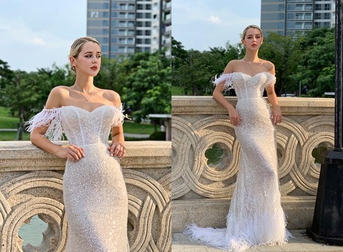NTK Linh Nga tạo dựng mẫu đầm cướilấy cảm hứng từ vẻ đẹp thanh lịch, quý phái của thiên nga trong bản nhạc kịch Hồ thiên nga. Chị ứng dụng chi tiết lông vũ - đón đầu xu hướng của mùa cưới 2019 - 2020, chọn lựa kiểu vai trễ,phom dáng gọn gàng cho cô dâu hiện đại. Vải kim sa dập ánh kim là chất liệu chủ đạo của thiết kế,được đính kết hàng nghìn viên pha lê Swarovski tạo sự lấp lánh. Ở mẫu đầm này, NTK tiết chế đường cắt để giữ phom dáng liền khối, áp dụng kỹ thuật dựng gọng corset, giúp siết eo tới 10 cm, định hình vòng hai thon nhỏ. Phần đuôi váy được đính 250m lông đà điểu ngoại nhập.Váy được bán với giá 100 triệu đồng, giá thuê 40 triệu đồng. Trang phục: Linh Nga Bridal