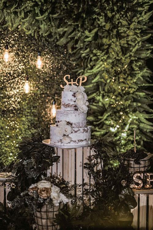 Bánh naked-cake của uyên ương với rất ít kem tươi phía ngoài và được điểm tô bởi ký tự tên 2 vợ chồng, hạt cà phê, hoa hồng leo.