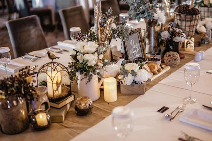Uyên ương trang trí bàn tiệc với hoa hồng, lá mimosa, nến trắng và thậm chí cả bánh ngọt, hạt cà phê.