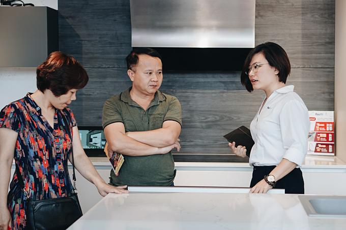 Chị Ngọc Mai (áo trắng) giải đáp thắc mắc của khách tham quan gian hàng tại Triển lãm quốc tế Vietbuild 2019.
