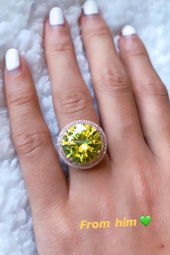 Chiếc nhẫn có gam màu vàng nổi bật, phản chiếu lấp lánh trên ngón tay áp út của Hoa hậu Hoàn vũ Việt  Nam 2015. Đây là lần thứ 2 Phạm Hương khoe được người yêutặng quà giá trị. Trước đó, vào dịp Valentine, cô nhận một chiếc nhẫn kim cương khác cùng lời cầu hôn ngọt ngào từ bạn trai doanh nhân Việt kiều.