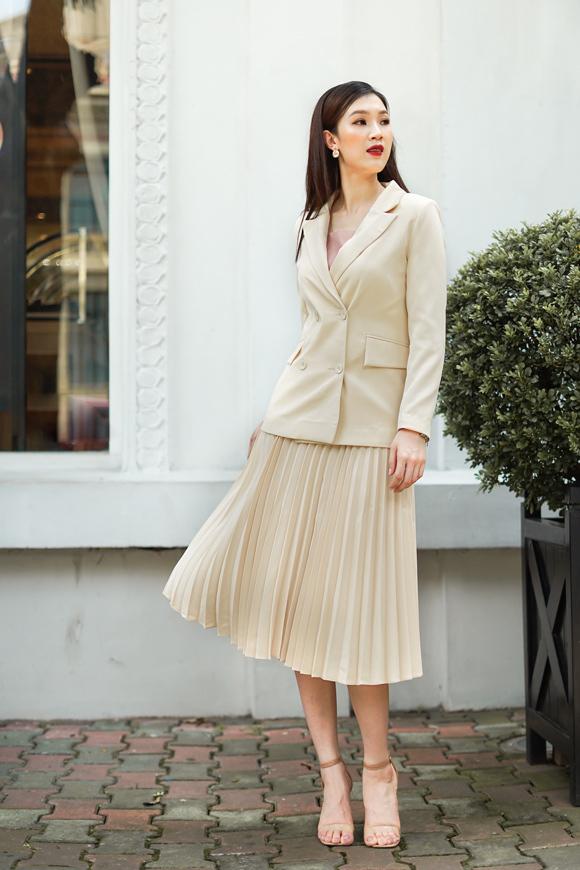 Để trẻ trung hơn, Phí Thùy Linh phối vest dáng suông với  chân váy xếp ly bay bổng. Cô không tham lam phụ kiện, chỉ sử  dụng sandal thanh thoát.