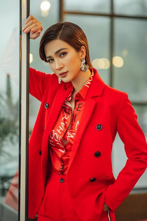 Kim Tuyến thu hút ánh nhìn với trang phục tông đỏ rực rỡ gồm áo sơ mi in chữ kết hợp quần âu thanh lịch.