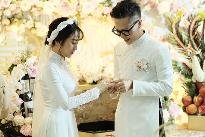 Minh Anh và chú rể Tâm Nguyễn nắm chặt tay, cười rạng rỡ khi thực hiện nghi thức cưới trước sự chứng kiến của người thân, bạn bè.