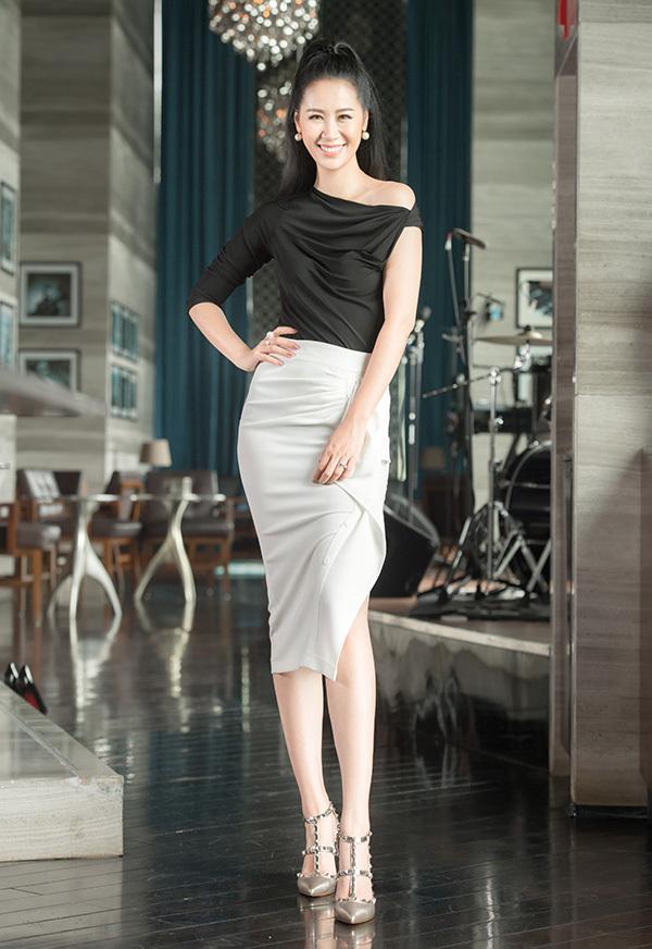 Sự đối lập màu sắc của chân váy nhún kèo trắng kết hợp với áo trễ vai đen tạo nên vẻ trẻ trung, điệu đà trong môi trường văn phòng.