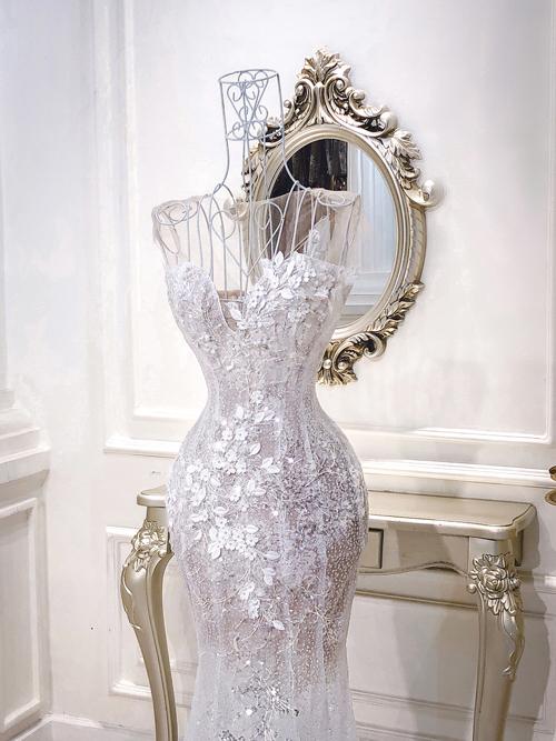 Để váy có độ ôm, NTK dựng nẹp trong suốt định hình phom dáng. Họa tiết dải hoa leo theo hình chữ S giúp dáng người của cô dâu mảnh mai, quyến rũ.
