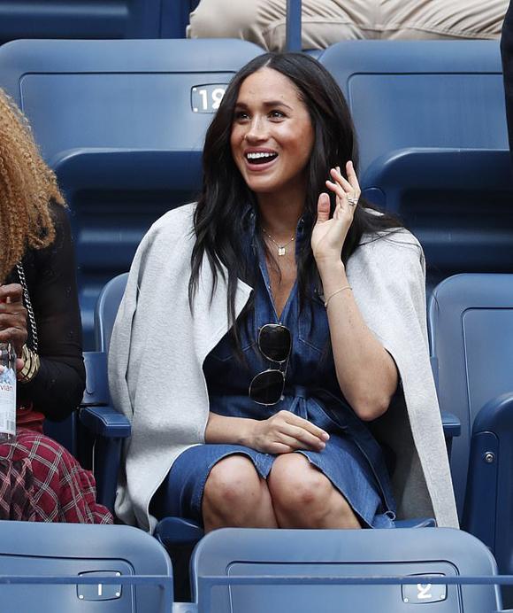 Meghan mặc váy bò ngồi trên khán đài cổ vũ bạn thân Serena Williams thi đấu tại New York hôm 7/9. Ảnh: Backgrid.