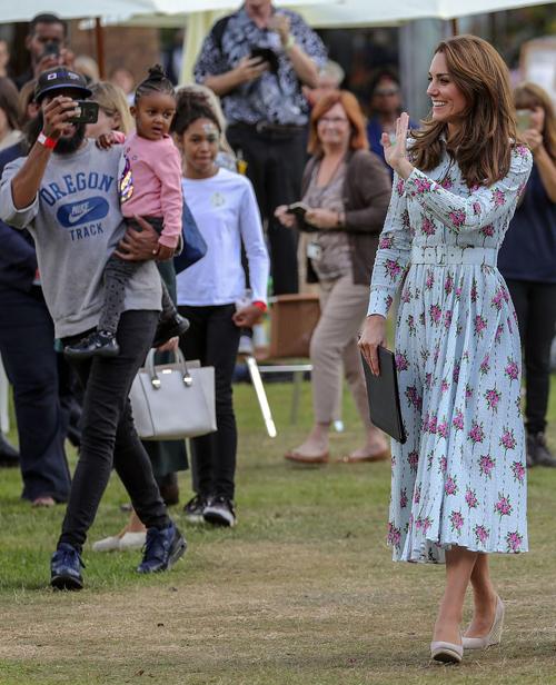 Bà mẹ ba con diện chiếc váy của nhà thiết kế Emelia Wickstead, trị giá 1.600 bảng (gần 2.000 USD), thắt thêm đai và đi giày cao gót màu nude. Cô luôn giữ thần thái rạng rỡ, vui vẻ khi trò chuyện với các khách mời hay các em nhỏ.