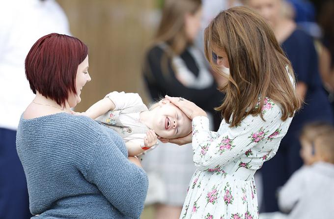 Nữ Công tước vui vẻ cười nói cùng hai mẹ con bé Matilda, 15 tháng tuổi, tại sự kiện.