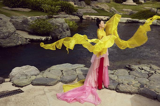 Mỹ Ngọc Bolero diện áo dài cách điệu của nhà thiết kế Thủy Nguyễn lấy cảm hứng từ sự bay bổng của sắc màu. Phần thân trên giữ nguyên thiết kế của áo dài truyền thống trong khi cánh tay và tà áo có bèo nhún như những dải lụa khi tung bay trong gió.