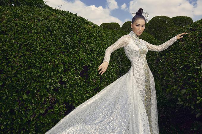 Áo dài phủ sequins của nhà thiết kế Việt Hùng với phần tà sau thướt tha giúp Mỹ Ngọc trở nên nổi bật hơn.